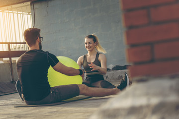 Couple exercising with a pilates ball