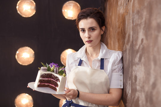 confectioner in a white apron on a pink background with a cake