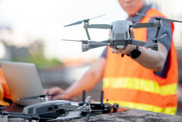 Young Asian engineer man working with drone laptop and smartphone at construction site. Using unmanned aerial vehicle (UAV) for land and building site survey in civil engineering project.