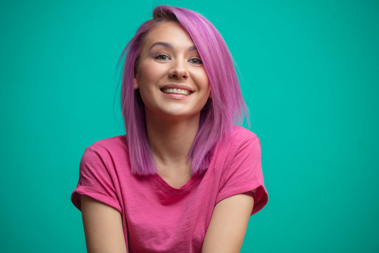 Young student enjoying her new trendy hairstyle, coloring her hair in pink, smiling broadly, feeling joy. Hipster girl with crimson hair feeling happiness after visiting hairdresser.