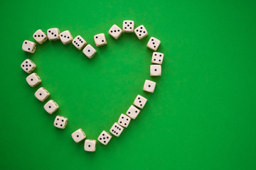 dice on a green background, heart-shaped