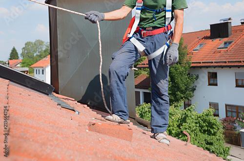 Kletterausrüstung Sicherung : Mann mit kletterausrüstung und seilsicherung sicherung für dach