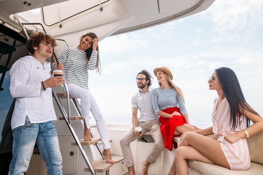 Young European people, dressed in marine style spending weekend at exclusive luxury sailing boat - Concept of friendship and travel with best friends.