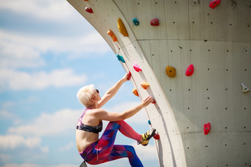 Photo of sports woman in leggings on wall for rock climbing against blue sky