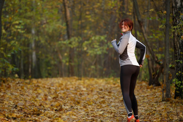 Image of happy woman in sports clothes on run in autumn