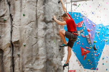 Photo from side of sports guy in red T-shirt training on climbing wall indoors
