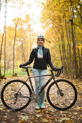 Image of woman in helmet, jeans next to bicycle