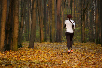 Picture from back of young sports girl in running through forest