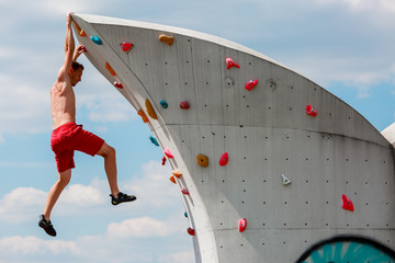 Photo of young sporty man in red shorts hanging on wall for rock climbing against blue sky with clouds
