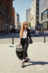 Blonde girl walking on the street with suitcase