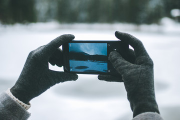 Gilr taking a photo of a beautiful mountain lake Synevyr in Ukraine on her black smartphone. Frozen lake covered with snow against dark winter forest
