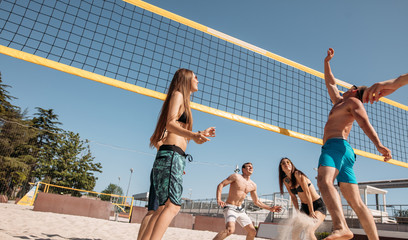 group of fit cheerful guys and girls, dressed in beach outfit, playing beach volleyball in sunny day duting theu summer holidays.