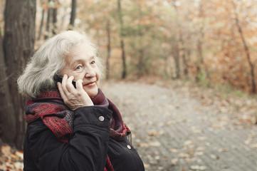 elderly woman talking on the phone in an autumn park