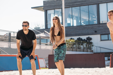Beach volleyball concept. Group of young jouful people preparing to beat off the ball in power serve, standing on court in sunny morning. Active recreation time during summer vacation in urban hotel.