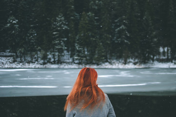 Handsome redhead girl looking in the distance. Splendid shady black mountain lake reflecting trees of forest behind her. Dreamy winter landscape of Carpathian mountains