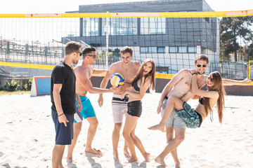 Caucasian guys and girls enjoying holiday vacation. Young happy people sunbathing on the beach, planning to play valleyball. Summer vacation at the resort.
