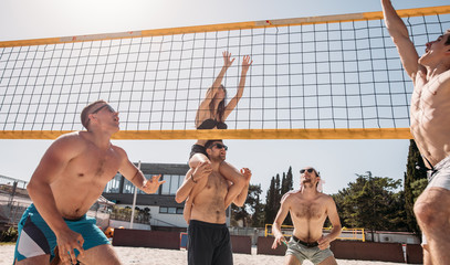 Beach volleyball amateur team players in action at sunny day under blue sky.