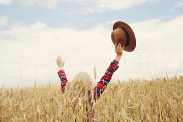Vista posterior de una mujer joven en un campo de trigo