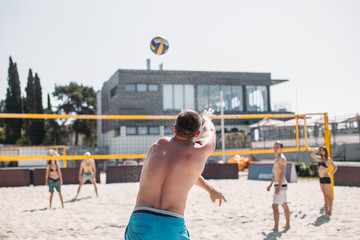 Volleyball beach player hits the ball, making power serve on the beach game.