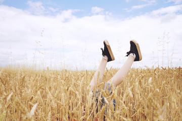 Piernas de un niño que sobresalen entre un campo de trigo
