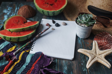 Woman`s or girl`s fashion beach season accessories, watermelon, starfish on rustic wooden background. Travel preparations concept, tropical summer holidays, selective focus, space for text