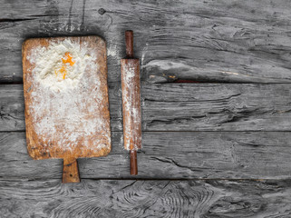 old kitchen wooden board with flour and eggs on a rustic table