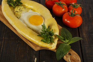 Khachapuri with fresh vegetables caucasian kitchen, close-up on a black wooden table. Adzharian khachapuri. View from above
