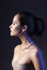 Beautiful brunette girl with naked shoulders and dark red lips make-up, wearing earrings and a pearl necklace, illuminated in blue.