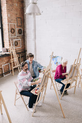High angle portrait of adult students  painting sitting by easels in art studio with female art teacher , copy space