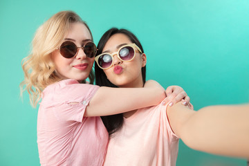 Portrait of pretty charming girls in casual outfits, wearing sunglasses shooting selfie , making duck faces, using smart phone isolated on studio blue background, close up