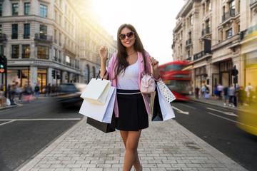 Attraktive, junge Frau mit Einkaufstaschen in der Hand auf der Regent Street in London beim Shoppen