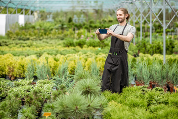Handsome gardener photographing beautiful plants during the work in the greenhouse