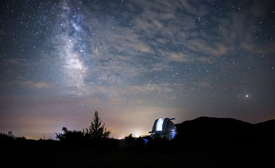 Open dome of a big telescope in an observatory in the background of the starry sky