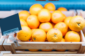 Box with oranges on stand in food store, nobody