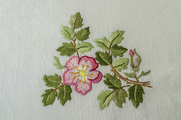 Pink flowers tea roses with a bud and leaves, embroidered a satin stitch on rough cotton fabric
