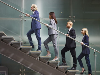 multinational and multiethnic corporate business people walking up stairs in a line