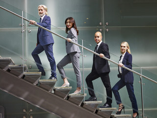 multinational and multiethnic corporate business people lined up on stairs of modern office building