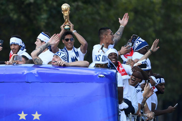 France's defender Raphael Varane holds the trophy as he celebrates with teammates on the roof of a bus while parading down the Champs-Elysee avenue in Paris