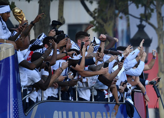 France's forward Olivier Giroud takes pictures as he celebrates with teammates on the roof of a bus while parading down the Champs-Elysee avenue in Paris