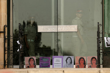 Photos of assassinated journalist Daphne Caruana Galizia are seen at the main entrance to Prime Minister Muscat's office at Auberge de Castille, as soldiers keep watch during a protest marking nine months since her murder in a car bomb, in Valletta