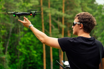 man in black T-shirt starts drone into the sky in the forest