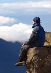 Resting man sitting on the rock above the crater Caldera de Taburiente, Island of La Palma, Canary Islands, Spain