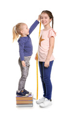 Little girls measuring their height on white background