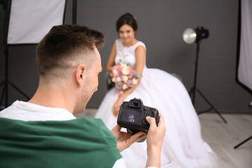 Professional photographer with camera and beautiful bride in studio