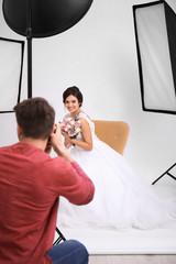 Professional photographer taking photo of beautiful bride in studio