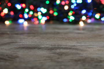 Wooden table and blurred Christmas lights on background