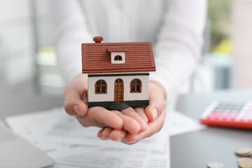 Woman holding house model on blurred background, closeup. Property tax