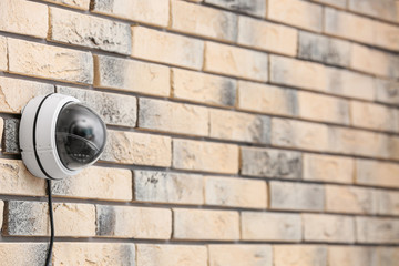 Modern security CCTV camera on brick wall