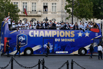 France's national soccer team players celebrate with teammates on the roof of a bus while parading down the Champs-Elysee avenue in Paris