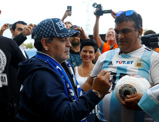 Diego Maradona signs a ball at the stadium before the match between Dinamo-Brest and Shakhtyor Soligorsk in Brest